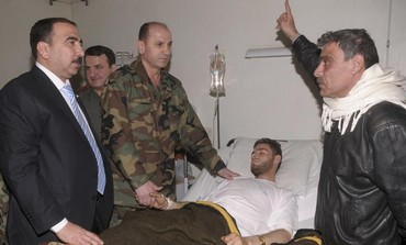 Syrian government officials and military personnel visit a victim of chemical weapons.