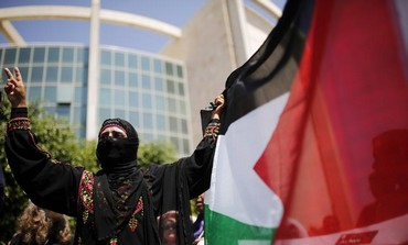 A protester holds flag during a demonstration in the southern Israeli city of Beersheba July 15, 201