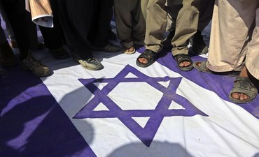 Demonstrators step on an Israeli national flag during a rally to mark Al-Quds (Jerusalem) Day.