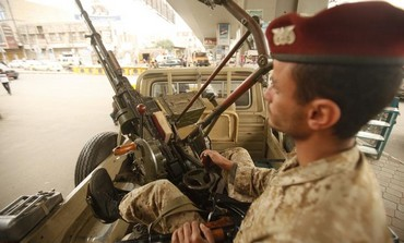 An army trooper sits beside a machinegun that is mounted on a patrol vehicle at Yemen checkpoint.