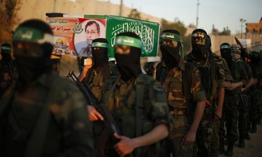 Hamas militants hold a mock coffin of Maysara Abu Hamdeya before a protest in the Gaza Strip.