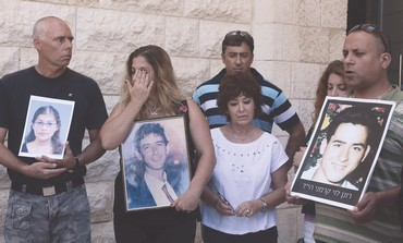 Opponenets of the deal to free terrorists hold photos of slain family members on Mount Herzl.