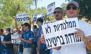 Staff from the Israel Broadcasting Authority gather outside the Finance Ministry, August 2013