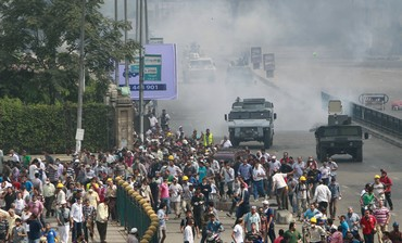 RIOT POLICE fire tear gas at protesters near Cairo University and Nahda Square, August 14, 2013