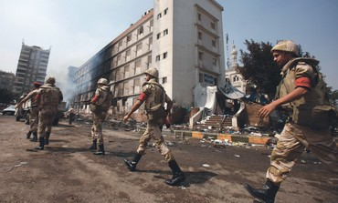 EGYPTIAN SOLDIERS walk past a burnt section of the Rabaa al-Adawiya mosque in Cairo.