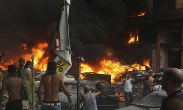 People gather around the site of an explosion in Beirut's southern suburbs, August 15, 2013.