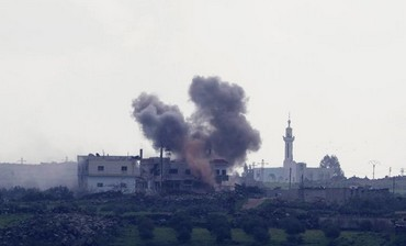 Smoke rises from shell explosions in the Syrian village of al-Jamlah.
