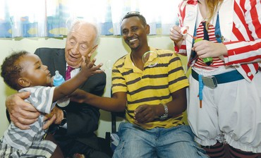 PRESIDENT SHIMON PERES holds a child at the East Talpiot 'tipat halav' center in Jerusalem yesterday