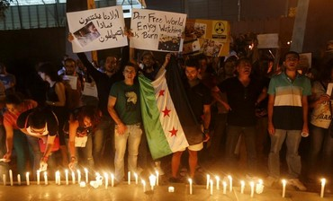 Civilians take part in a vigil in solidarity with Syrians killed by an alleged gas attack.