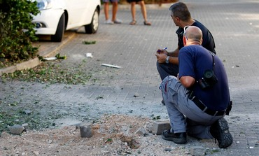 Israeli police survey damage to a village near Nahariya following Thursday's rocket attack.