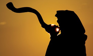 A man sounds a Kudo-horn shofar on a mountain in the Judean Desert