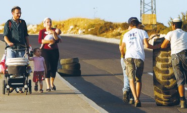 TWO YOUTH push a tire up a hill in the community of Beit El in the West Bank.