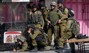 IDF troops take up position during clashes with Palestinian stonethrowers in Hebron. Sept. 22, 2013.