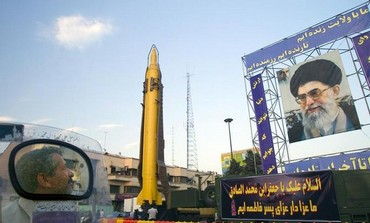 A motorcyclist looks at an Iranian-made Ghadr-F missile during a war exhibition