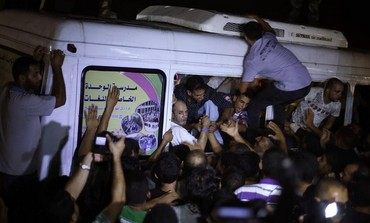 Palestinians greet freed prisoners upon their arrival near Erez crossing, August 14, 2013.