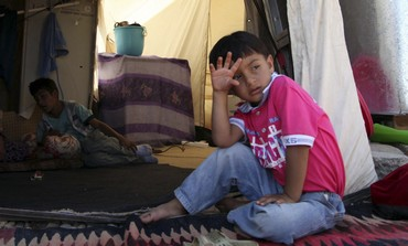 Syrian refugee boy sits outside a tent at the Arbat refugee camp
