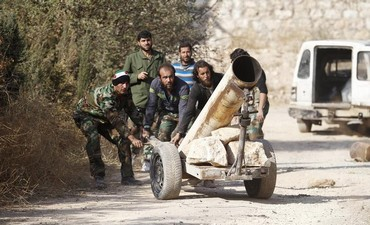 Syrian opposition fighters drag a rocket launcher near the 80th Brigade bas