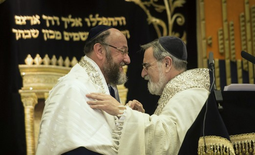 Former chief rabbi, Jonathan Sacks (R), congratulates new chief rabbi, Ephraim Mirvis.