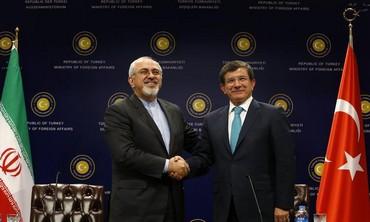 Iranian FM Mohammad Javad Zarif (L) shakes hands with his Turkish counterpart Ahmet Davutoglu.