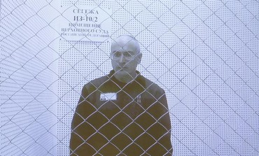 Mikhail Khodorkovsky is seen on a screen during an appeal for a reduced sentence in Russia