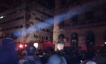 Crowds gather outside a security building in Mansoura