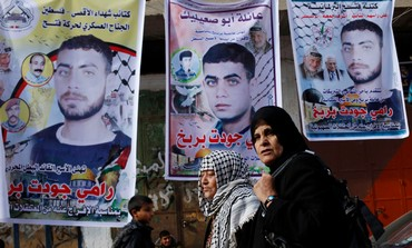 Gaza women walk past posters of Palestinian prisoners.Kosher restaurant.