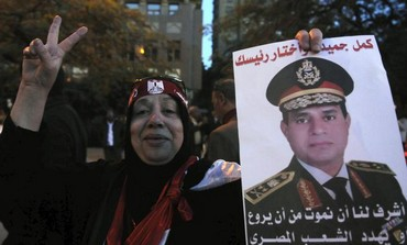 An Egyptian woman holds up a picture of army general Abdel al-Sisi