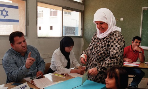 An Israeli Arab woman casts her vote at a polling station in the 'Triangle' town of Umm al-Fahm