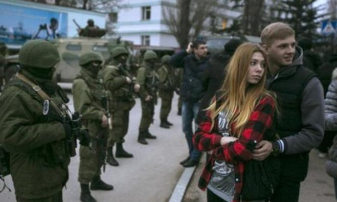 A Ukrainian couple stands next to Russian soldiers in the Crimean town of Balaclava.