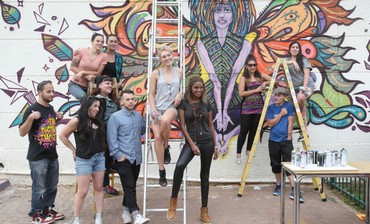 former Miss Israel, joins in painting a wall.