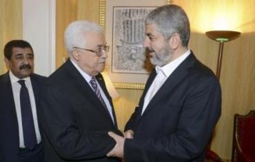 Palestinian President Mahmoud Abbas (L) shakes hands with Hamas chief Khaled Mashaal in Doha May 5,
