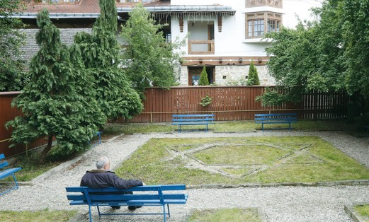 A MAN sits in the garden of the childhood home of Elie Wiesel