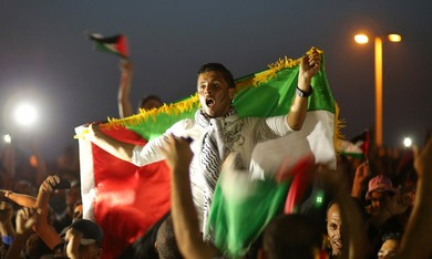 Palestinians celebrate after their national soccer team defeated the Philippines