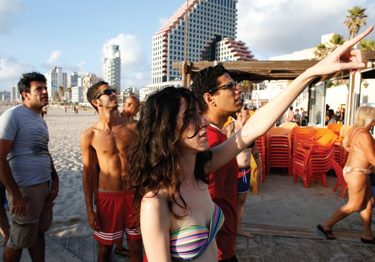 Beach-goers look at explosions