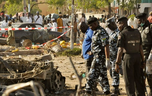 Security forces inspect the wreckage of a car believed to be used in Kano attack.