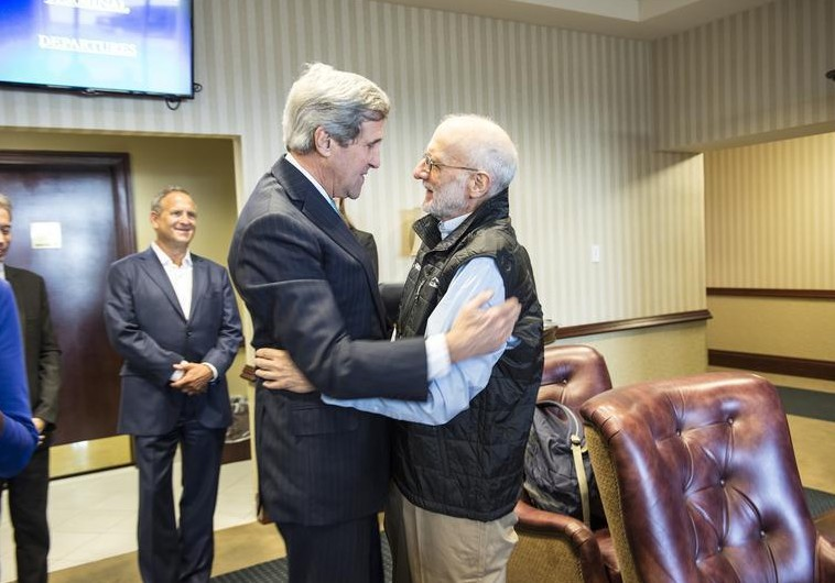 US Secretary of State John Kerry (L) embraces Alan Gross at Joint Base Andrews