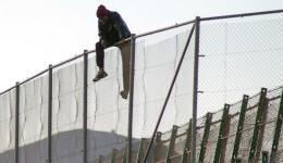 A MAN sits on a fence in Melilla, a Spanish enclave in North Africa.