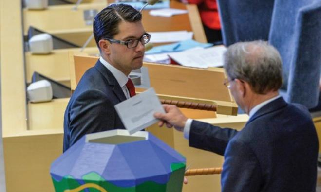 The leader of the Sweden Democrats Jimmie Akesson hands over his ballot to parliament speaker.