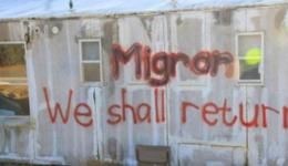 Graffiti on the side of a Migron home.