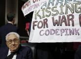 Former United States Secretary of State Henry Kissinger sits calmly as protesters demand his arrest