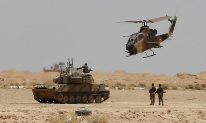 Jordanian military helicopter flies over an armored vehicle near the Karameh border crossing