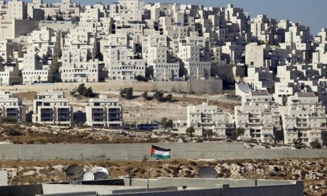 A Palestinian flag flutters in front of the Jerusalem neighborhood of Har Homa
