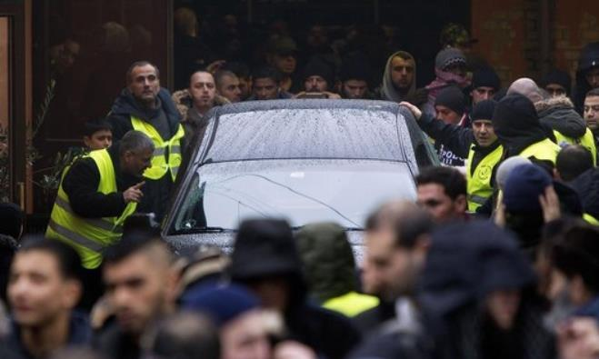 Mourners surround the hearse with Omar Abdel Hamid El-Hussein