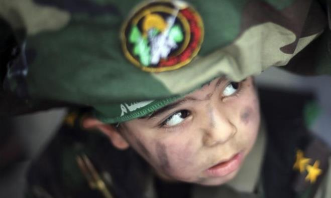 A Palestinian boy wearing the headband of Hamas