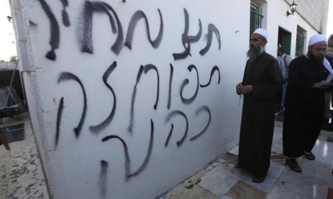 A Palestinian villager looks at Hebrew graffiti spray-painted on a wall at the entrance of a mosque