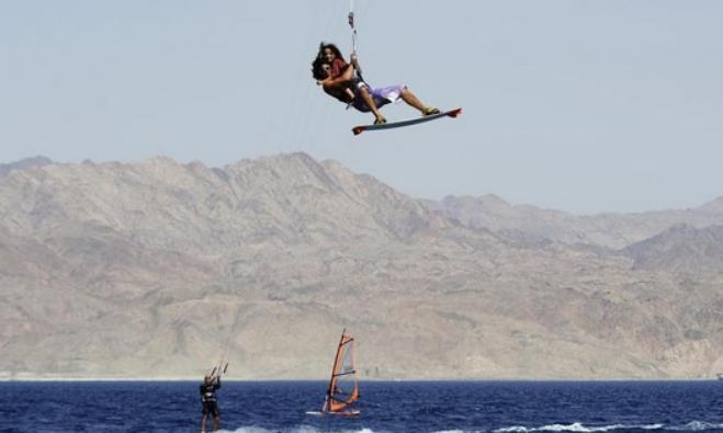 Israeli kite surfer Eli Zarka gets airborne with five-year-old Michael Smila (R) in Eilat