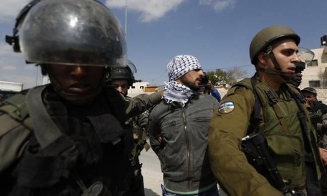 Israeli security forces detain a Palestinian near the West Bank town of Abu Dis