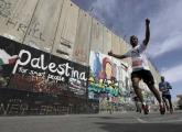 Participants run past the controversial Israeli barrier during the Palestine Marathon in Bethlehem