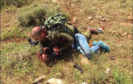 An IDF soldier subdues a Palestinian assailant after he was stabbed near a West Bank checkpoint
