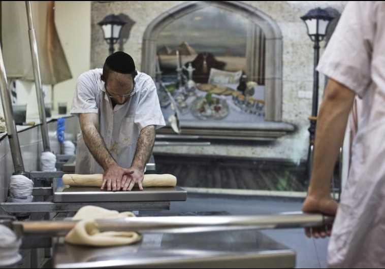 An ultra-Orthodox Jewish man kneads dough as he prepares matza